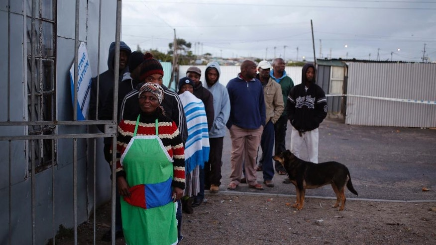 Voters stand in line outside a polling station during municipal elections in Khayelitsha township on the outskirts of Cape Town, South Africa, Wednesday, Aug. 3, 2016. South Africans are voting in municipal elections in which the ruling African National Congress seeks to retain control of key metropolitan areas despite a vigorous challenge from opposition parties. (AP Photo/Schalk van Zuydam)