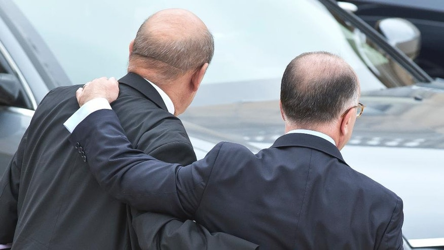 French Defense Minister Jean-Yves Le Drian, , left, bits farewell to French Interior Minister Bernard Cazeneuve, right, after the last cabinet meeting before official vacations at the Elysee Palace, Wednesday, Aug 3, 2016. (AP Photo/Michel Euler)