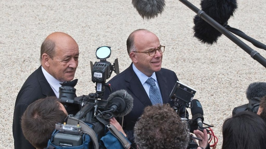 French Defense Minister Jean-Yves Le Drian, , left, and French Interior Minister Bernard Cazeneuve, right, speak to reporters after the last cabinet meeting before official vacations at the Elysee Palace, Wednesday, Aug 3, 2016. (AP Photo/Michel Euler)