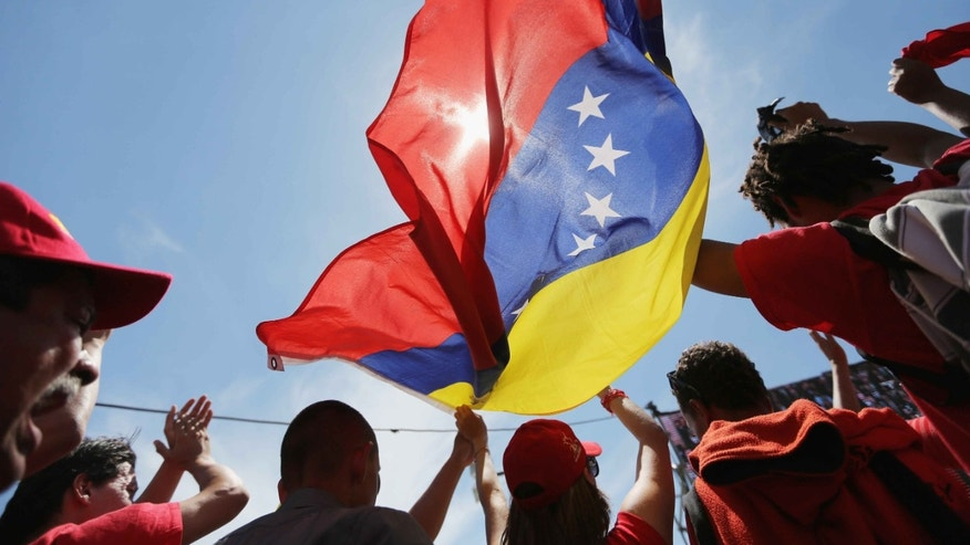CARACAS, VENEZUELA - MARCH 08: People wave the national flag while watching a live broadcast of the funeral for Venezuelan President Hugo Chavez outside the Military Academy on March 8, 2013 in Caracas, Venezuela. Countless Venezuelans have paid their last respects to Chavez and more than 30 heads of state were expected to attend the funeral today.  (Photo by Mario Tama/Getty Images)