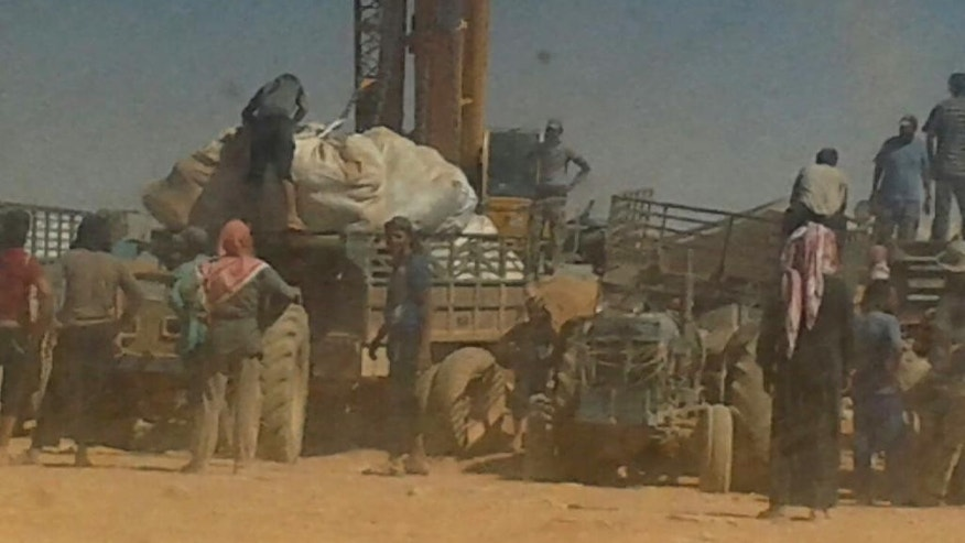 ADDS DATE - Cranes drop food across the Jordan-Syria border to community leaders charged with distributing equitably the supplies to the 64,000-person refugee camp called Ruqban on Thursday, Aug. 4, 2016 . Refugees there have been without food and medicine, and with little water, after the border was sealed following a car bomb killed seven soldiers six weeks ago. (AP Photo)
