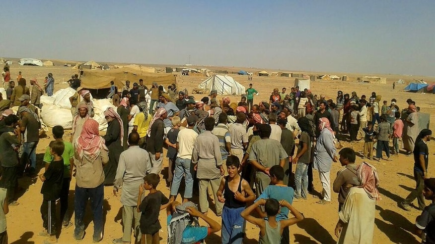 ADDS DATE - People gather to take basic food stuffs and other aid from community leaders charged with distributing equitably the supplies to the 64,000-person refugee camp called Ruqban on the Jordan-Syria border on Thursday, Aug. 4, 2016. Refugees there have been without food and medicine, and with little water, after the border was sealed following a car bomb killed seven soldiers six weeks ago. (AP Photo)