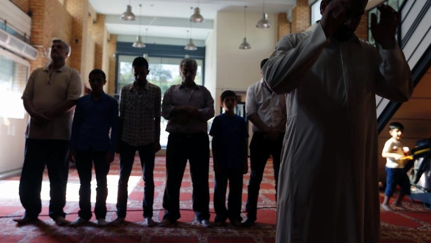 Muslim migrants who live in Greece pray at the Greek-Arab Cultural Center, a Muslim prayer site in Athens, Thursday, Aug. 4, 2016. Lawmakers in Greece have approved construction of a state-funded mosque near central Athens, a proposal that triggered dissent within the country's coalition government amid a heated public debate on how manage the migrant crisis. (AP Photo/Thanassis Stavrakis)