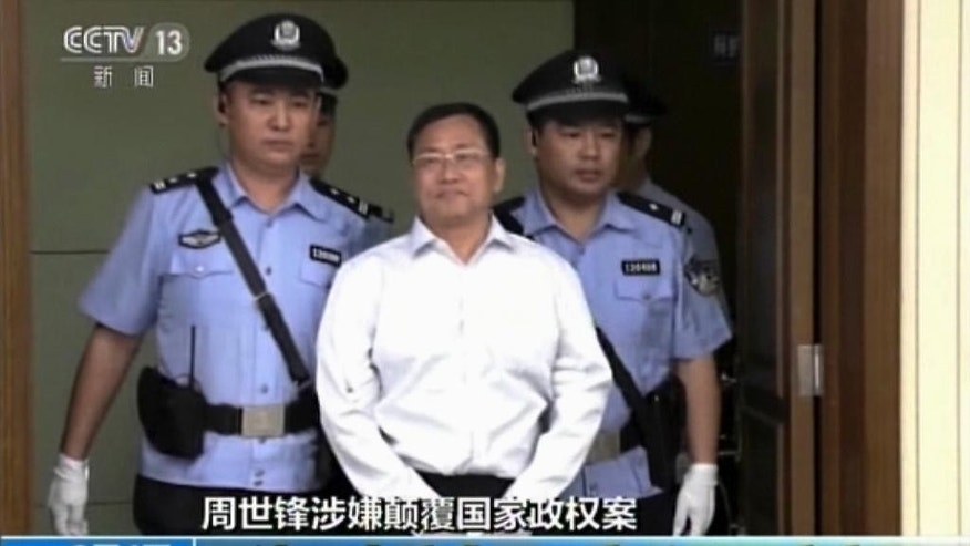 In this image from video, Zhou Shifeng, center, is escorted by police officers upon his arrival for his trial at the Tianjin No. 2 Intermediate People's Court in northern China's Tianjin Municipality Thursday, Aug. 4, 2016. Zhou, a Chinese lawyer was in court Thursday in the third of a series of subversion trials demonstrating the ruling Communist Party's determination to shut down independent human rights activists and government critics. (CCTV via AP Video)