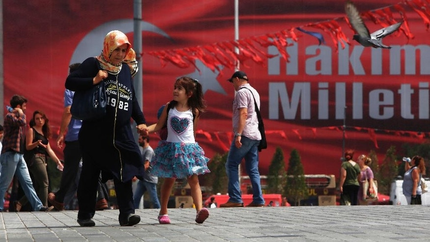 A woman walks with a child at Taksim square in Istanbul, on Thursday, Aug. 4, 2016. The Turkish government has launched a sweeping crackdown on the movement of Fethullah Gulen, a former Erdogan ally who lives in self-imposed exile in Pennsylvania, since the attempted coup, with nearly 70,000 people suspended or dismissed from jobs in the civil service, judiciary, education, health care, the military and the media.  (AP Photo/Petros Karadjias)