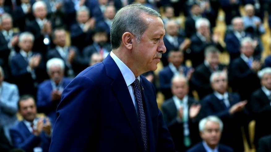 Turkey's President Recep Tayyip Erdogan arrives in a conference of the heads of chambers of commerce in Ankara, Turkey, on Thursday, Aug. 4, 2016. Erdogan vowed to go after businesses linked to a US-based Muslim cleric he accuses of having been behind Turkey's failed July 15 coup. The Turkish government characterizes the movement of Fethullah Gulen, who lives in self-imposed exile in Pennsylvania, as a terrorist organization. (Kayhan Ozer/Presidential Press Service, Pool Photo via AP)