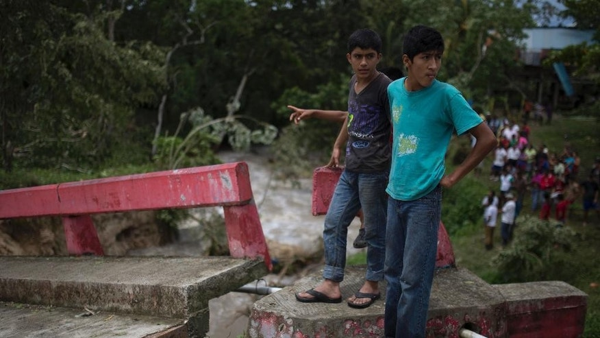 Two men stand on a portion of a bridge damaged by Hurricane Earl in the Arroyito neighborhood, in Melchor de Mencos, Guatemala, on the Peten border with Belize, Thursday, Aug. 4, 2016. Earl deteriorated to a weak tropical storm Thursday as it passed over northern Guatemala en route to southern Mexico. (AP Photo/Luis Soto)