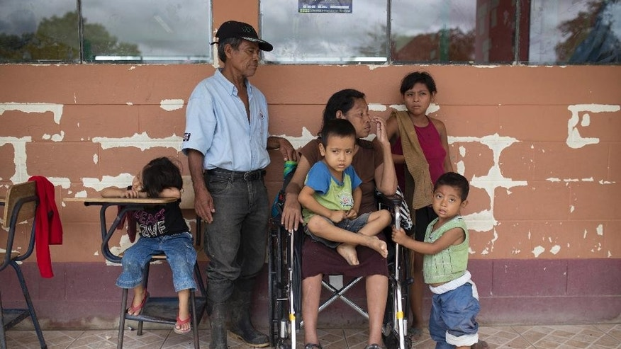 A family sits in a hallway of school turned into temporary shelter for residents seeking refuge from Hurricane Earl in Melchor de Mencos, in the Arroyito neighborhood, in Melchor de Mencos, Guatemala, on the Peten border with Belize, Thursday, Aug. 4, 2016. Earl deteriorated to a weak tropical storm Thursday as it passed over northern Guatemala en route to southern Mexico. (AP Photo/Luis Soto)