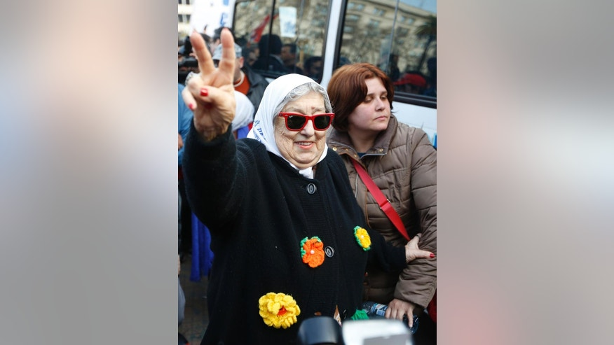 Hebe de Bonafini, president of the Madres de Plaza de Mayo human rights group, flashes a vee as she leaves the historic square after taking part in the traditional weekly march in Buenos Aires, Argentina, Thursday, Aug. 4, 2016. Argentine police have Bonafini for refusing to appear for questioning into the alleged embezzlement of public funds meant for a low-income housing project. (AP Photo/Jorge Saenz)