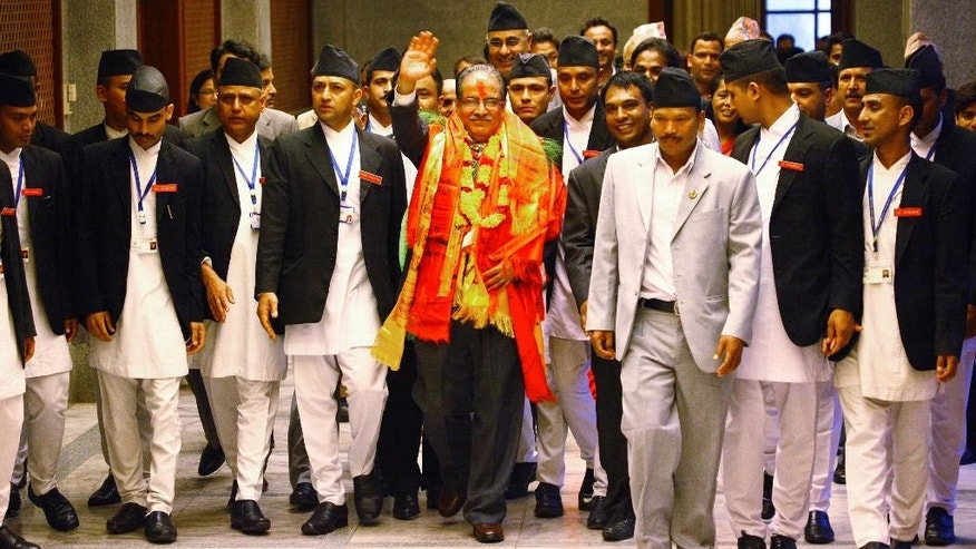 Nepal's newly-appointed prime minister Pushpa Kamal Dahal, center, waves as he comes out of the parliament after being elected in Kathmandu, Nepal, Wednesday, Aug.3, 2016. Nepal's parliament elected the former communist rebel leader as the country's new prime minister Wednesday who would now lead a coalition government and likely give continuation to political instability in the Himalayan nation. (AP Photo/Bikram Rai)
