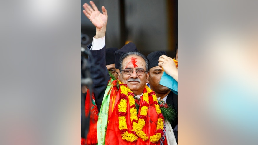 Nepal's newly-appointed prime minister Pushpa Kamal Dahal, waves to the media in Kathmandu, Nepal, Wednesday, Aug.3, 2016. Nepal's parliament elected the former communist rebel leader as the country's new prime minister Wednesday who would now lead a coalition government and likely give continuation to political instability in the Himalayan nation.(AP Photo/Bikram Rai)
