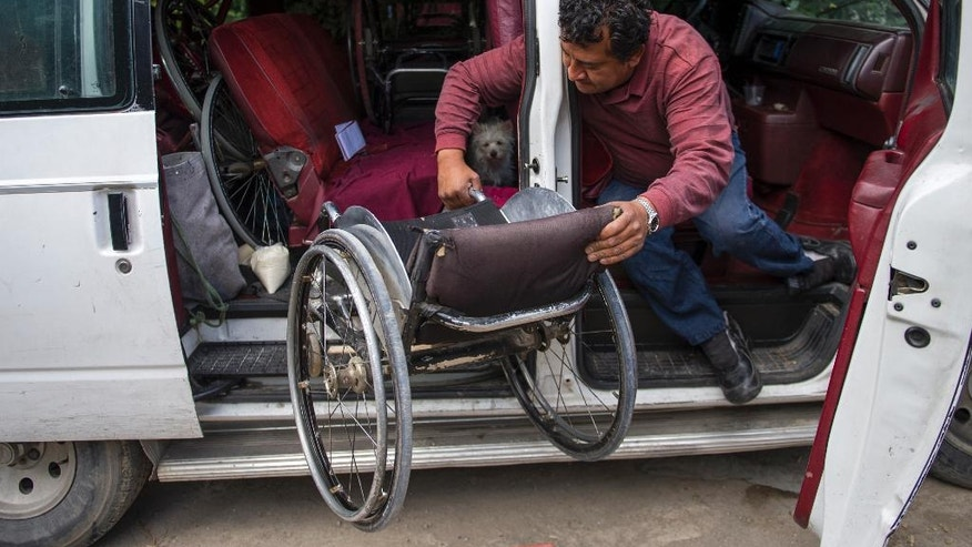 In this July 21, 2016 photo, Salvador Espinoza lifts his wheelchair into his van outside of his home in Chalco, Mexico. Espinoza spends his days in a wheelchair due to a spinal cord injury that left him paralyzed from the waist down. But when Espinoza mounts his horse and tightens the back brace that helps him keep upright in the saddle, he transforms into a charro, or Mexican cowboy. (AP Photo/Nick Wagner)