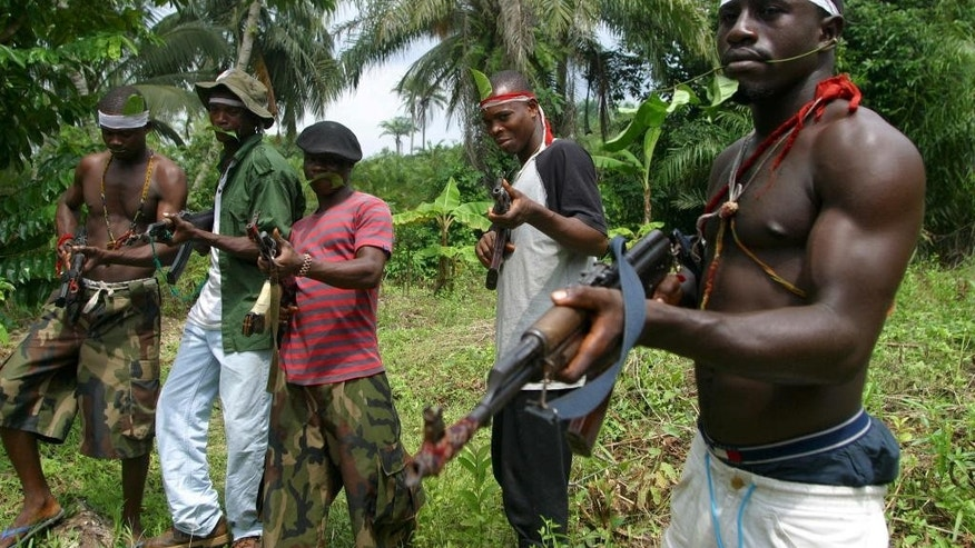 FILE- In this Friday June. 25, 2004 file photo, Ijaw millitants hold AK-47 rifles as they stand guard at Okorota, near Port Harcourt, Nigeria. Nigeria's government has resumed paying stipends to former militants, on the week of Thursday Aug. 4 2016, even as security forces mount air bombardments and ground assaults reported to have killed scores of fighters disrupting petroleum production in the oil-rich Niger Delta. (AP Photo/George Osodi file)