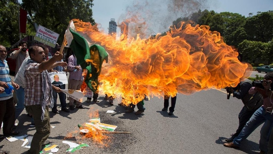 Kashmiris burn a representation of an Indian flag as they chant slogans outside the Foreign Office in Islamabad, Pakistan, Thursday, Aug. 4, 2016. People have rallied in the capital against the imminent visit of India's Interior Minister Rajnath Singh to attend the SAARC organization meeting.  (AP Photo/B.K. Bangash)