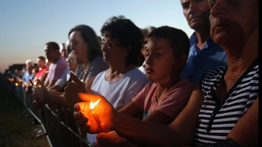 "People hold candles during a memorial service for the victims of the Croatian ""Storm"" offensive, to mark the 21th anniversary in the village of Busije, some 25 kilometers (15 miles) west of Belgrade, Serbia, Thursday, Aug. 4, 2016. Croatia is marking its military operation with victory celebrations, while Serbia considers the ""Storm"" offensive a war crime that resulted in the exodus of most Serbs living in Croatia. (AP Photo/Darko Vojinovic)"