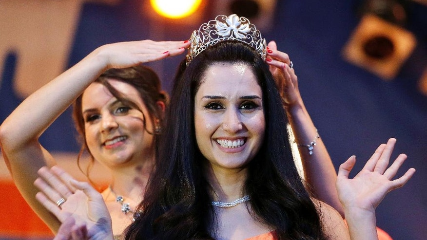 Being crowned by her predecessor, 26-year-old former Syrian refugee Ninorta Bahno is crowned, becoming the first former refugee in Germany to be crowned Wine Queen of Trier,  in the town of Trier, southern Germany, Wednesday, Aug. 3, 2016.  Ninorta Bahno was a Syrian refugee who fled to Germany in 2012.  (AP Photo/Michael Probst)