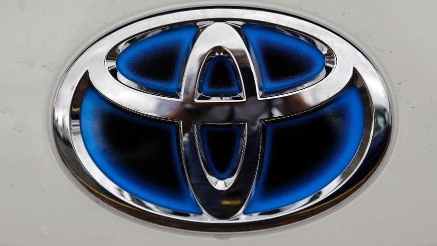 FILE - In this Monday, Jan. 15, 2015, file photo, the emblem on a new Toyota is shown at a dealership in Brandon, Fla. Toyota's much ballyhooed plug-in hybrid Prius Prime is being pushed back by several months, with the new sales date set for late this year or early next year. Toyota Motor Corp. said Wednesday the launch dates were being delayed for Japan, but not for the U.S. and Europe because they were set to follow Japan from the start. It was unclear what the dates were for any of the regions. (AP Photo/Chris O'Meara, File)