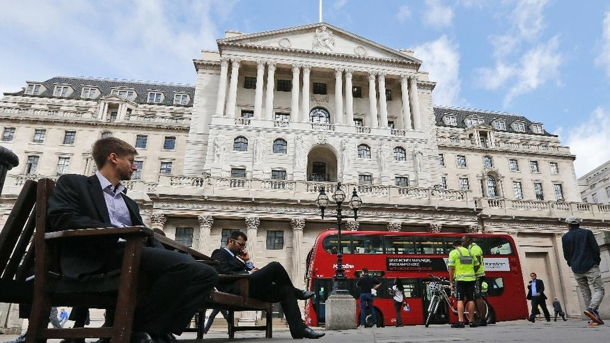 A London bus passes the Bank of England while people sit on a bench in London, Thursday, Aug. 4, 2016. The Bank of England is expected to cut interest rates close to zero and possibly inject billions in new money into the economy to help it endure the shock of the vote to leave the European Union. (AP Photo/Frank Augstein)