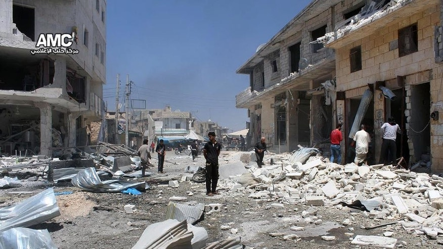 This photo provided by the Syrian anti-government activist group Aleppo Media Center (AMC), shows Syrian citizens inspecting damaged shops after airstrikes hit a market in Atareb, west of the divided city of Aleppo, Syria, Tuesday, Aug 2, 2016. The Britain-based Syrian Observatory said at least 11 people, including five children were killed when bombs were dropped in a market in Atareb. (Aleppo Media Center via AP)