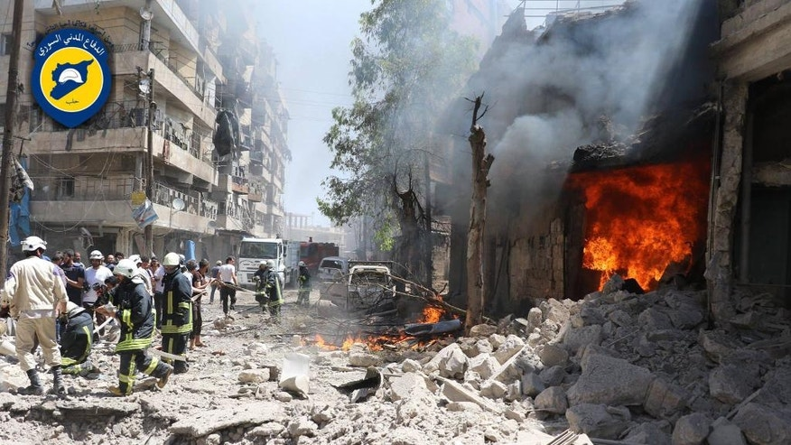 FILE - This file photo taken on June 8, 2016 provided by the Syrian Civil Defense Directorate in Liberated Province of Aleppo, which has been authenticated based on its contents and other AP reporting, shows Syrian civil defense workers, left, gather at a street which attacked by warplanes, in Aleppo, Syria. Fierce fighting and airstrikes continue in Syria's northern city of Aleppo as insurgents try to break a siege on opposition-held eastern districts in a counteroffensive to government advances. But Syria's war, now in its sixth year, is raging beyond Aleppo, claiming dozens of lives every day. (Civil Defense Directorate in Liberated Province of Aleppo via AP, File)