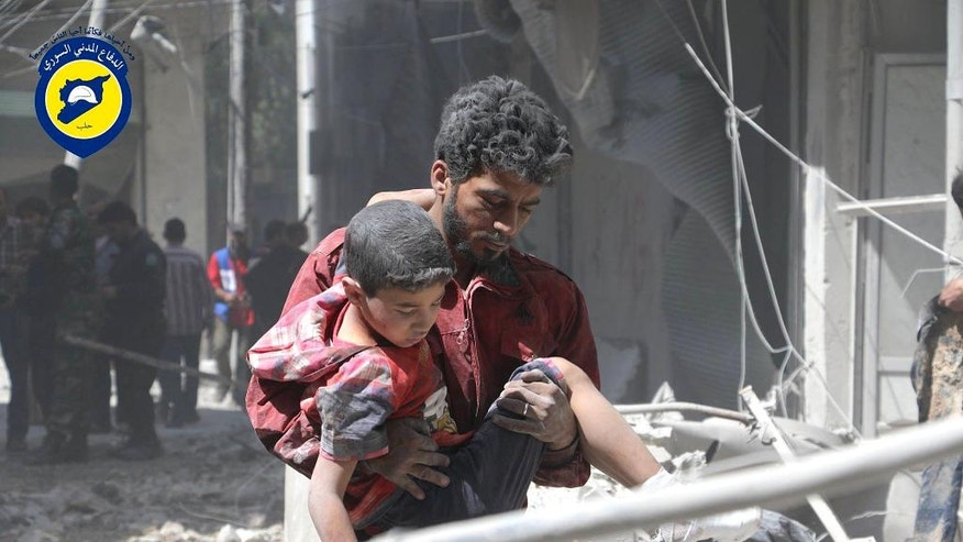 FILE - In this file photo taken on May 31, 2016 provided by the Syrian Civil Defense Directorate in Liberated Province of Aleppo, which has been authenticated based on its contents and other AP reporting, shows Syrian man carries an injured boy, in Aleppo, Syria. Fierce fighting and airstrikes continue in Syria's northern city of Aleppo as insurgents try to break a siege on opposition-held eastern districts in a counteroffensive to government advances. But Syria's war, now in its sixth year, is raging beyond Aleppo, claiming dozens of lives every day. (Civil Defense Directorate in Liberated Province of Aleppo via AP, File)