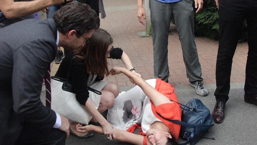 In this Monday, Aug. 1, 2016 photo, Fan Lili, the wife of imprisoned activist Gou Hongguo, lies on the ground in tears as members of foreign diplomats trying to help her following an incident with plainclothes police officer outside the Tianjin No. 2 Intermediate People's Court in northern China's Tianjin Municipality. In halting televised confessions and emotional courtroom testimony, Chinese lawyers and activists held in a government crackdown have intoned the same ominous refrain: Shadowy foreign forces are funding, directing and encouraging activities bent on destabilizing China's government and smearing its reputation. (AP Photo/Gerry Shih)