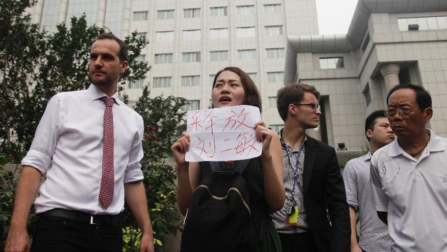 "In this Monday, Aug. 1, 2016 photo, Li Wenzu, center, wife of imprisoned lawyer Wang Quanzhang, holds a paper that reads ""Release Liu Ermin"" stage a protest next to members of foreign diplomats and supporters of a prominent Chinese human rights lawyer and activists outside the Tianjin No. 2 Intermediate People's Court in northern China's Tianjin Municipality. In halting televised confessions and emotional courtroom testimony, Chinese lawyers and activists held in a government crackdown have intoned the same ominous refrain: Shadowy foreign forces are funding, directing and encouraging activities bent on destabilizing China's government and smearing its reputation. (AP Photo/Gerry Shih)"