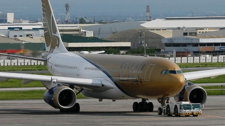 A Gulf Air passenger plane is towed by ground crew for inspection after it made an emergency landing about 25 minutes into the flight Friday, Aug. 5, 2016, at the Ninoy Aquino International Airport at suburban Pasay city south of Manila, Philippines. TThe Gulf Air flight, carrying 219 people on a flight to Bahrain made an emergency landing in the Philippines, returning there Friday after the pilot reported intense heat in the left engine of the Airbus 330-200 shortly after take-off, and smoke was seen in the cabin, airport officials said. Ma. .(AP Photo/Bullit Marquez)