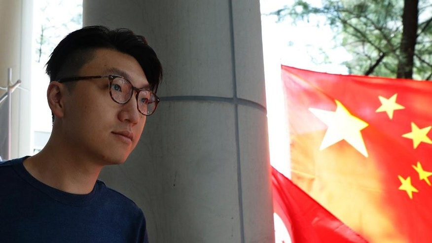 "Hong Kong localist leader Edward Leung Tin-kei walks past a Chinese national flag outside a court after he was charged with rioting in Hong Kong, Friday, Aug. 5, 2016. Amid a dispute over candidates excluded on political grounds, Hong Kong's government on Friday posted the names of those approved to run in the territory's most contentious Legislative Council elections since reverting to Chinese rule almost two decades ago. The placard reads ""Punish rioters severely, pay back in prison"".(AP Photo/Kin Cheung)"