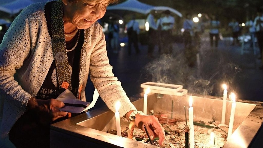 A woman lights a candle as she prays for the atomic bomb victims in front of the cenotaph at the Hiroshima Peace Memorial Park in Hiroshima, western Japan, early Saturday Aug. 6, 2016. Japan marked the 71st anniversary of the atomic bombing on Hiroshima.  (Tsuyoshi Ueda/Kyodo News via AP)