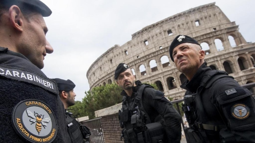 Carabinieri (Italian paramilitary police) special unit's officers patrol the area next to the Colosseum, visible in background, in Rome, Friday, Aug. 5, 2016. Anti-terrorism measures have been tightened in Rome. They include the stationing of police cars and van at the end of a boulevard that runs past the Colosseum, and police patrols and surveillance along Via del Corso, a long street lined with clothing shops and which also runs by the premier's office. (Claudio Peri/ANSA via AP)