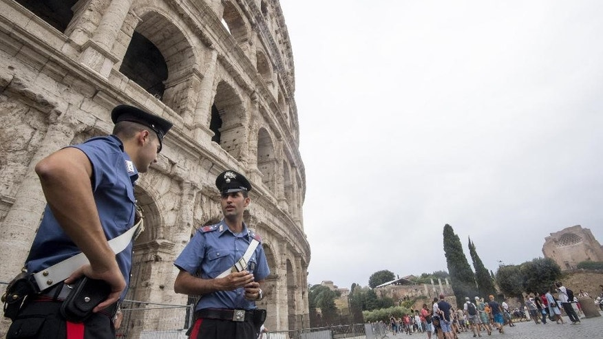 Carabinieri (Italian paramilitary police) officers patrol outside the Colosseum, in Rome, Friday, Aug. 5, 2016. Anti-terrorism measures have been tightened in Rome. They include the stationing of police cars and van at the end of a boulevard that runs past the Colosseum, and police patrols and surveillance along Via del Corso, a long street lined with clothing shops and which also runs by the premier's office. (Claudio Peri/ANSA via AP)