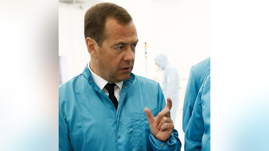 In this Tuesday, Aug. 2, 2016 photo Russian Prime Minister Dmitry Medvedev visits a factory in Zelenograd, outside Moscow, Russia.  More than 160,000,  people have signed a petition on Friday Aug. 5, 2016 calling on President Vladimir Putin to sack Medvedev. The petition lamented the poor performance of the government and said a man like Medvedev should not lead the Cabinet.  (Dmitry Astakhov/Sputnik, Government Pool Photo via AP)