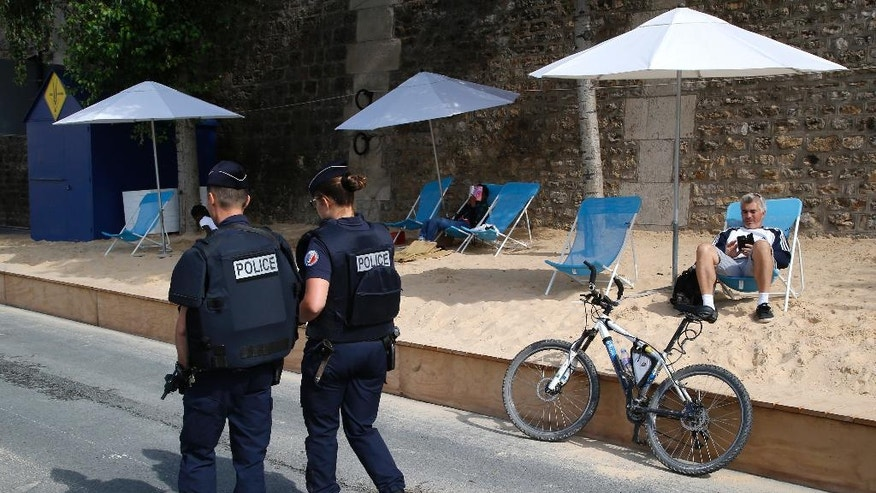 French police officers patrol at Paris Plage (Paris Beach) Friday, Aug. 5, 2016 in Paris. Paris Plage is an artificial beach set up on the right bank of the Seine river with palm trees, outdoor showers and hammocks. Numerous summer festivals have been canceled because maximal security cannot be assured despite additional injection of security forces. (AP Photo/Michel Euler)