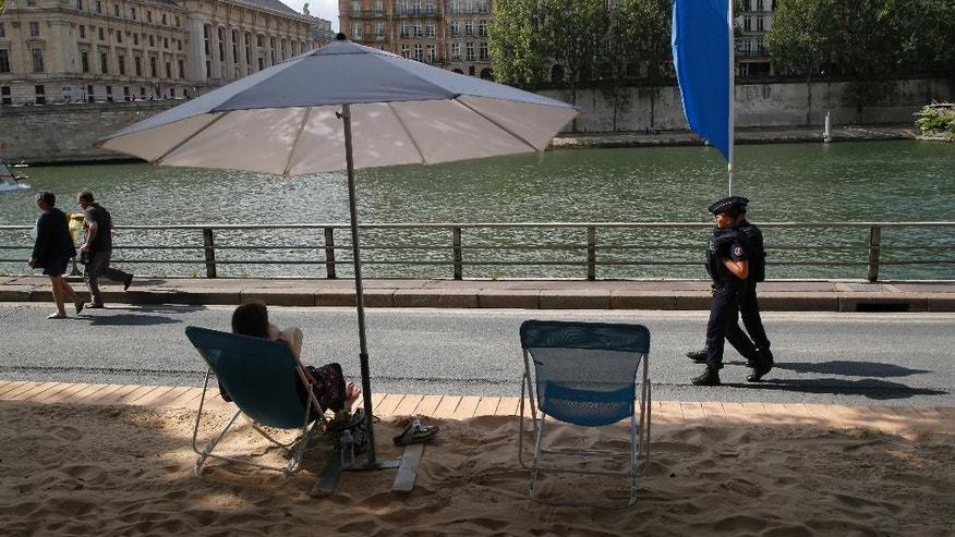 French police officers patrol over the Seine river at Paris Plage (Paris Beach) Friday, Aug. 5, 2016 in Paris. Paris Plage is an artificial beach set up on the right bank of the Seine river with palm trees, outdoor showers and hammocks. Numerous summer festivals have been canceled because maximal security cannot be assured despite additional injection of security forces. (AP Photo/Michel Euler)
