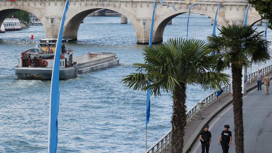 French police officers patrol along the Seine river at Paris Plage (Paris Beach) Friday, Aug. 5, 2016 in Paris. Paris Plage is an artificial beach set up on the right bank of the Seine river with palm trees, outdoor showers and hammocks. Numerous summer festivals have been canceled because maximal security cannot be assured despite additional injection of security forces. (AP Photo/Michel Euler)