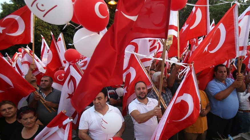 Turkish Cypriot demonstrators wave Turkish and Turkish Cypriot flags during a mass rally in support of Turkey's Prime Minister Recep Tayyip Erodgan following a failed coup that aimed to oust him, during a protest in the breakaway Turkish Cypriot half of the capital Nicosia on Friday, Aug. 5, 2016. Mostly right-wing political parties and groups urged supporters to turn up for the rally that follows similar pro-Erdogan and anti-coup demonstrations in other European countries. (AP Photo/Philippos Christou)