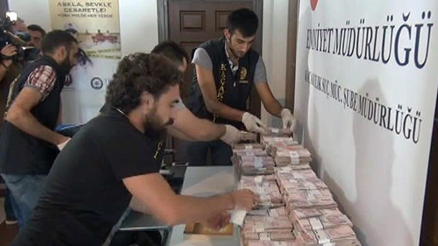 Police collect cash money seized in raids on the home and business of one suspected follower of a Muslim cleric accused of instigating an abortive coup in Istanbul, Friday, Aug. 5, 2016.  There were the two shotguns, one pistol, ammunition, a fake identity card, and three one dollar bills, among evidence seized in a series of raids, as the government conducts a sweeping crackdown in the wake of the July 15 attempted coup that left more than 270 people dead. ( (Sinan Bilgili/DHA via AP)