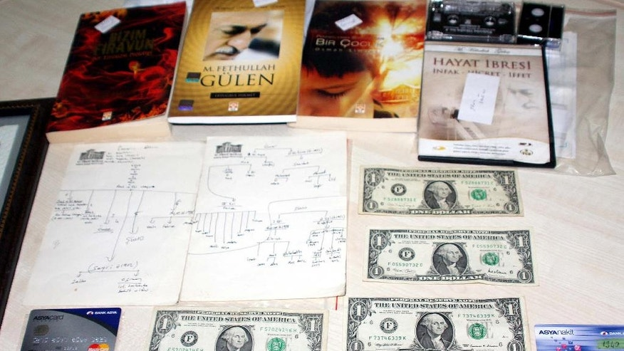 In this Wednesday, Aug 3, 2016 photo, shows dollars cash money, Visas cards and books displayed after police raids on the home and the business of one suspected follower of a Muslim cleric accused of instigating an abortive coup in Gaziantep, Turkey.   There were the two shotguns, one pistol, ammunition, a fake identity card, and three one dollar bills, among evidence seized in a series of raids, as the government conducts a sweeping crackdown in the wake of the July 15 attempted coup that left more than 270 people dead. (Hasan Kirmizitas/DHA via AP)