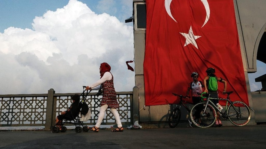 A woman passes with her child by two cyclist as they stand by a giant Turkey flag at the Galata bridge in Istanbul, on Thursday, Aug. 4, 2016. The Turkish government characterizes the movement of Fethullah Gulen, who lives in self-imposed exile in Pennsylvania, as a terrorist organization. (AP Photo/Petros Karadjias)