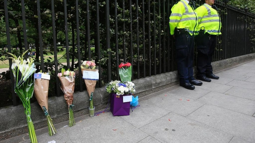 Floral tributes rest against railings Thursday Aug. 4, 2016, near the scene of a fatal stabbing on Wednesday night in Russell Square, London. London police say they have found no signs of radicalization in a knife attack which killed an American woman and injured five other people in London's Russell Square.  (Jonathan Brady/PA via AP)