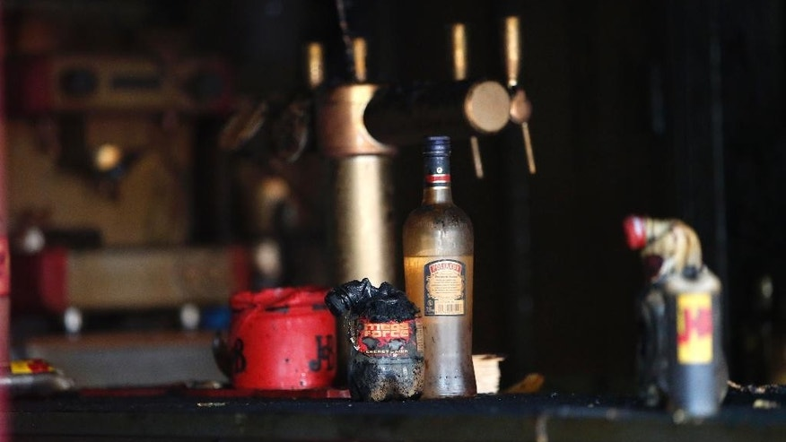 Bottles are pictured in the bar where a fire broke in Rouen, western France, Saturday Aug.6, 2016. A fire swept through a Friday night birthday party at a bar in the Normandy city of Rouen, killing at least 13 people and injuring six others, French authorities said. (AP Photo/Kamil Zihnioglu)
