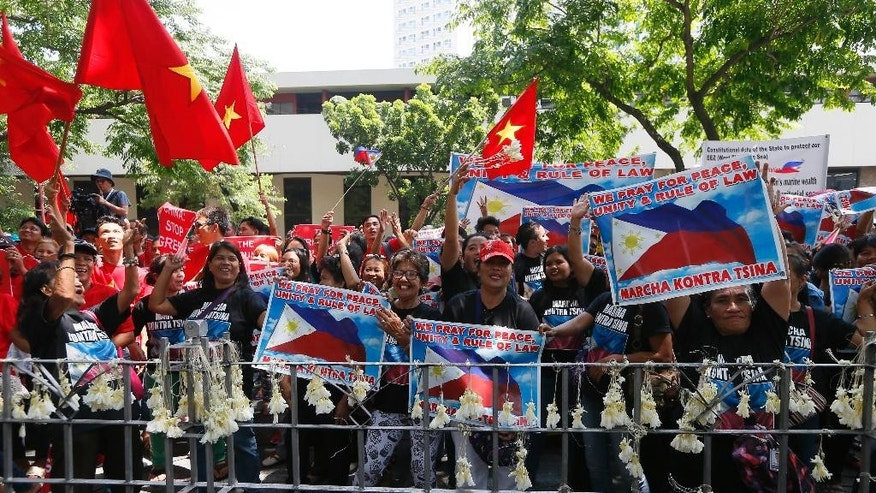 "Filipinos and Vietnamese residents shout slogans while displaying placards during a rally outside the Chinese Consulate to call on China to respect the international arbitration ruling favoring the Philippines on the disputed group of islands in the South China Sea Saturday, Aug. 6, 2016, in the financial district of Makati city east of Manila, Philippines. The protesters denounced China over its continued ""defiance of the Tribunal ruling."" (AP Photo/Bullit Marquez)"