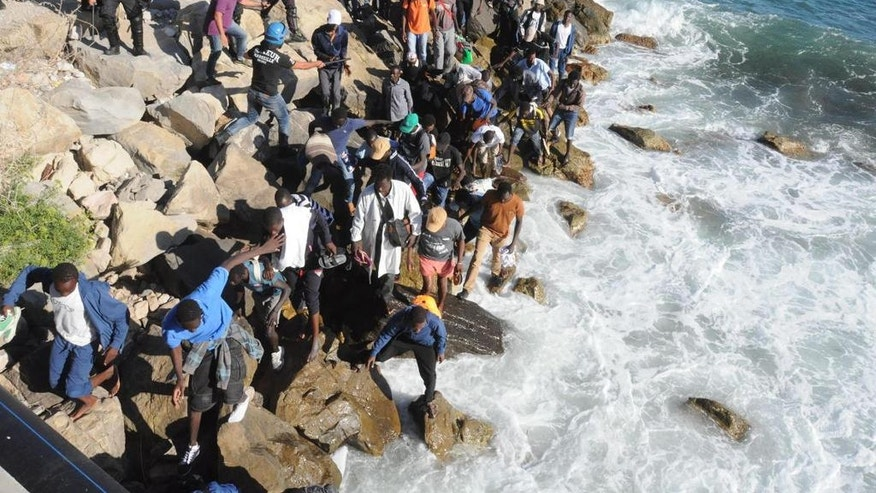 Migrants walk on the rocks as they try to get to the sea past a Police cordon in Ventimiglia, an Italian town on the border with France, Friday, Aug. 5, 2016. Italian and French Police reportedly fired tear gas trying to prevent the migrants from reaching France. (Fabrizio Tenerelli/ANSA via AP)