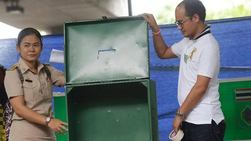 Thai officers show an empty box before the start of vote in a referendum on a new constitution at a polling station in Bangkok, Thailand, Sunday, Aug. 7, 2016. Thais voted Sunday in a referendum on a new constitution that critics say is tailor-made for the military government to stay in control for several years and entrench a new, quasi-democratic system that gives vast powers to appointed officials. (AP Photo/Sakchai Lalit)
