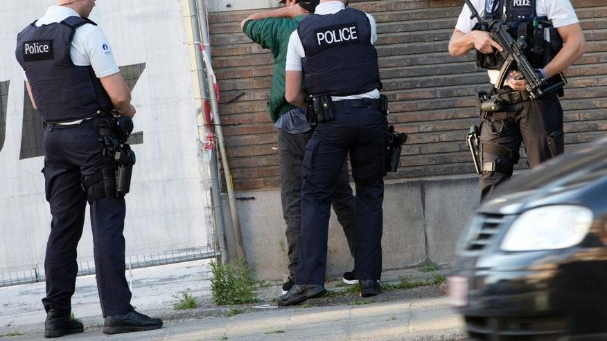 "Police officers check the identification of a man near the police headquarters in Charleroi, Belgium on Saturday, Aug. 6, 2016.  Two female officers were attacked and wounded by a man wielding a machete and shouting ""Allahu Akhbar"" outside a police station in the Belgian city of Charleroi on Saturday, police said.  (AP Photo/Virginia Mayo)"