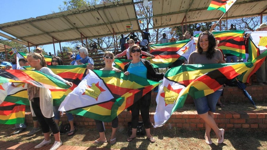 Zimbabweans stand displaying flags, during the 36th over of the test cricket match between New Zealand and Zimbabwe, at Queens Sports Club in Bulawayo, Zimbabwe,  Saturday, Aug. 6, 2016. (AP Photo/Tsvangirayi Mukwazhi)
