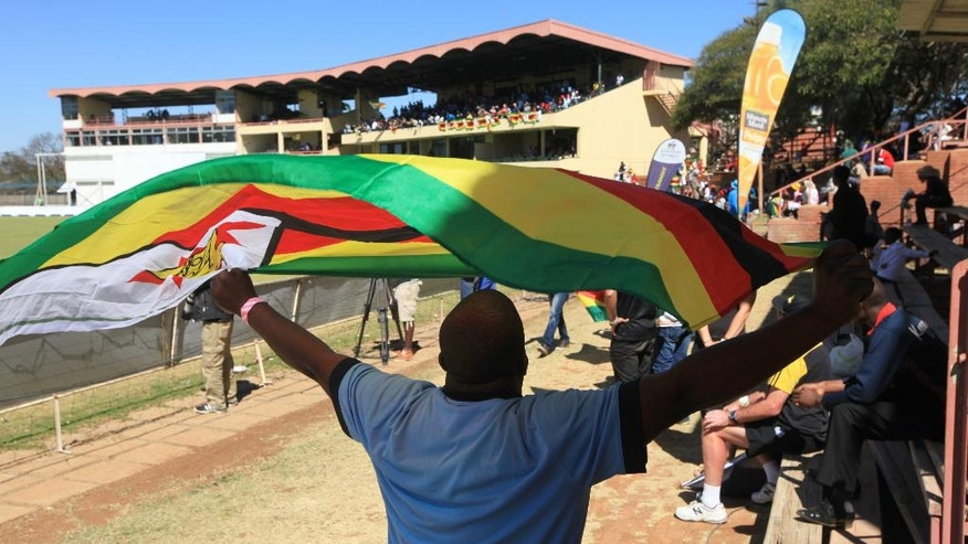 A man carries the Zimbabwean flag,  during the 36th over of the test cricket match between New Zealand and Zimbabwe, at Queens Sports Club in Bulawayo, Zimbabwe,  Saturday, Aug. 6, 2016. (AP Photo/Tsvangirayi Mukwazhi)