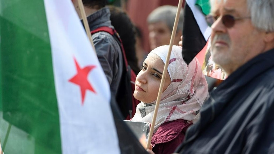 Syrian protesters demonstrate against the bombing of Aleppo in Syria, on the Place des Nations in front of the European headquarters of the United Nations in Geneva, Switzerland, Friday, August 5, 2016. (Martial Trezzini/Keystone via AP)
