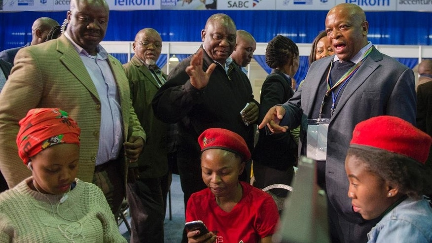 Deputy President Cyril Ramaphosa centre back, greets opposition Economic Freedom Front party members at the results center in Pretoria, South Africa, Friday, Aug. 5, 2016.  With 95 percent of votes counted the ruling ANC appears to have suffered its biggest electoral blow since it won power at the end of the apartheid era 22-years ago. (AP Photo/Herman Verwey)